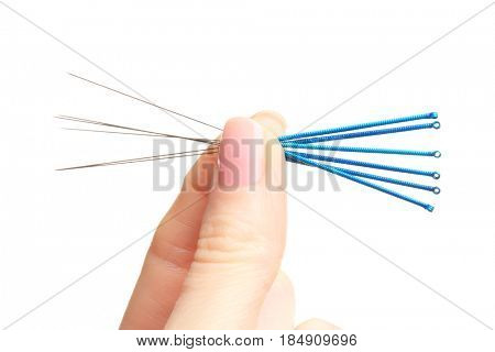 Female fingers with needles for acupuncture on white background, closeup