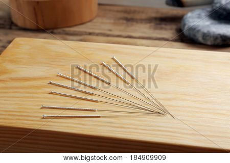 Acupuncture needles on wooden board