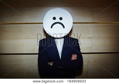 Upset businessman in white shirt and suit covered his face with sad mask while standing with arms crossed against wooden wall