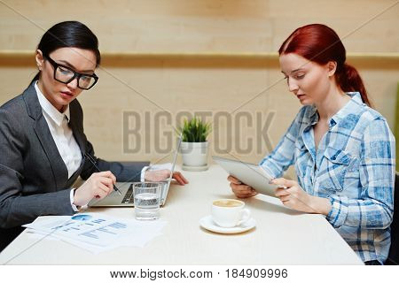 Pretty young businesswoman in formalwear analyzing results of accomplished work and taking necessary notes while her colleague in casualwear working on digital tablet, waist-up portrait