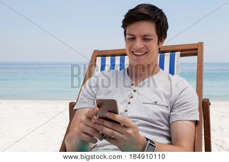 Smiling man sitting on sunlounger and using mobile phone on the beach