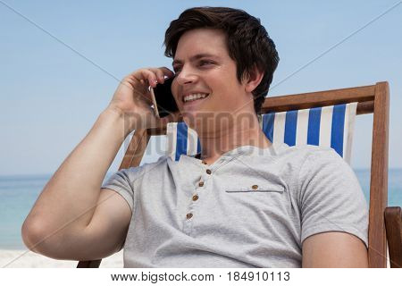 Smiling man sitting on sunlounger and talking on mobile phone on the beach