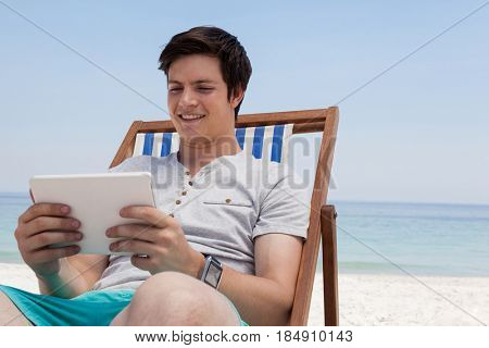 Smiling man sitting on sunlounger and using digital tablet on the beach