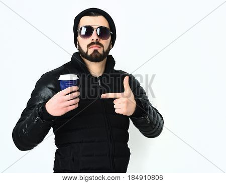Bearded man short beard. Brutal caucasian serious hipster with moustache holding blue plastic cup or mug of coffee wearing black nylon jacket and sunglasses isolated on white background