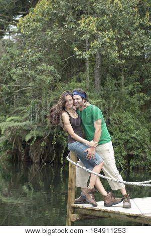 Hispanic couple hugging on pier