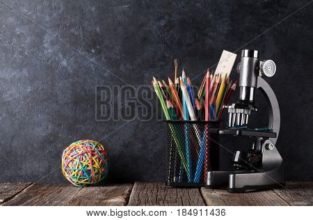 Supplies and microscope in front of chalk board. Back to school concept with copy space