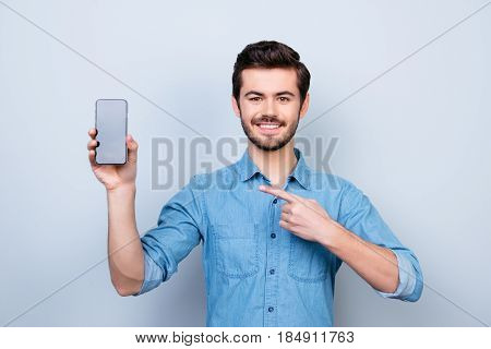Portrait Of Happy Young Man Pointing With His Finger On The Screen Of His Smartphone On Light Blue B