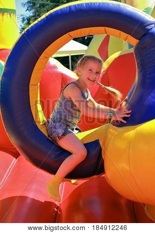 Joyful girl jumping on a trampoline inflatable
