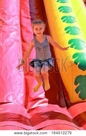 Girl jumping on inflatable attractions in park outdoor