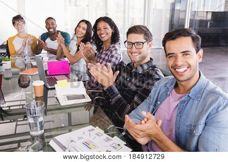 Portrait of business team clapping while sitting at glass table in creative office