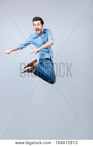 Happy Young Guy Is Jumping And Pointing On His Right. He Is In Casual Wear And Wide Open Mouth