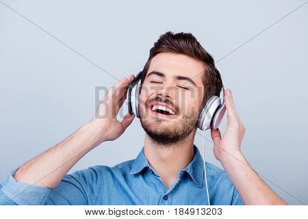 Close Up Portrait Of Cheerful Young Man Enjoying Listening To His Favourite Song With Closed Eyes In