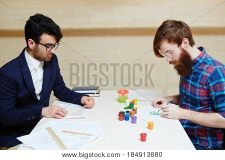 War of logic vs creativity: concentrated office worker in suit wrapped up in drawing architecture project with pencil and ruler while other man in casualwear creating picture with brush and gouache