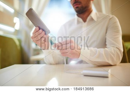 Close-up shot of bearded man in white shirt charging his smartphone with power bank while sitting in cozy small coffeehouse