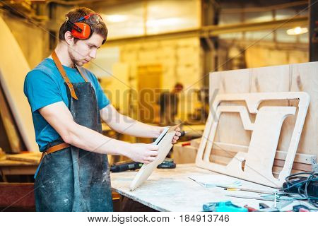Portrait of focused young man working in carpenting studio, fitting parts for wooden furniture
