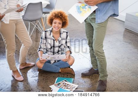 Portrait of smiling businesswoman sitting amidst colleagues standing on floor at creative office