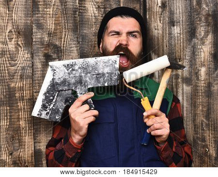 bearded builder man long beard brutal caucasian hipster with moustache in uniform holding various building tools: hammer roller paint spatulas with satisfied face on brown wooden studio background