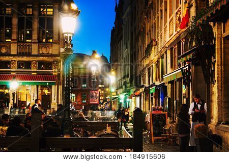 BRUSSELS, BELGIUM - MARCH 5, 2014: Illuminated houses at the Grand Place square at night in Brussels, Belgium. People at the restaurant, cafe
