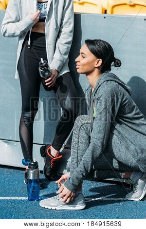 Athletic young women in sportswear resting with sports bottles on stadium running women concept