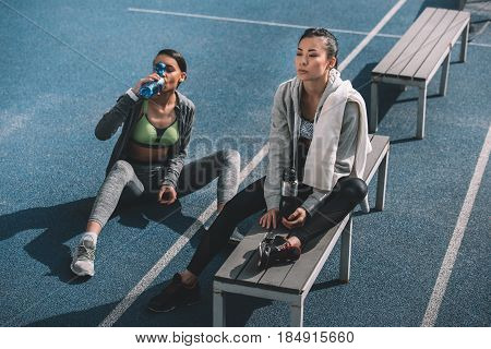 Tired young sportswomen with sports bottles resting on running track stadium