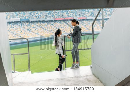 full length of two young sportswomen standing at handrail on stadium