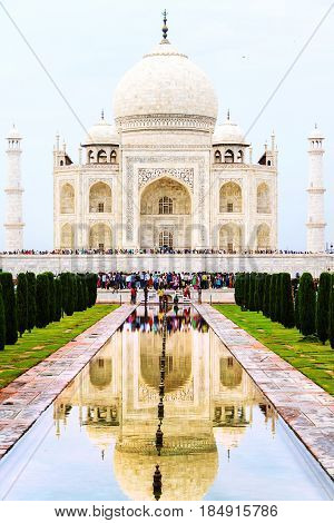 Agra, India. Taj Mahal mausoleum in the city of Agra, India during the day. Crowd of people, reflection in the pond