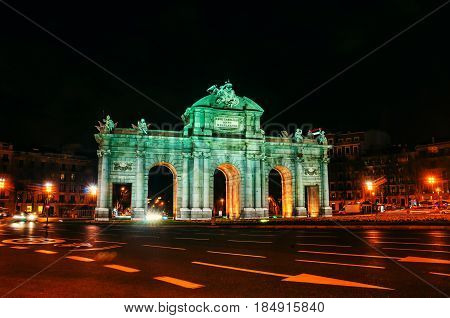 Madrid, Spain. Night view of The Puerta de Alcala at night - a monument in the Independence Square in Madrid, Spain. Car light trails, illumination, dark sky