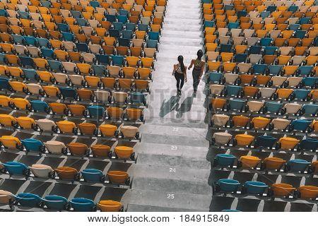 two sportswomen running on stadium stairs running women concept