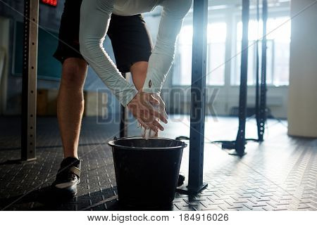 Low section of unrecognizable muscular man covering hands with talk over bucket before weightlifting practice in gym