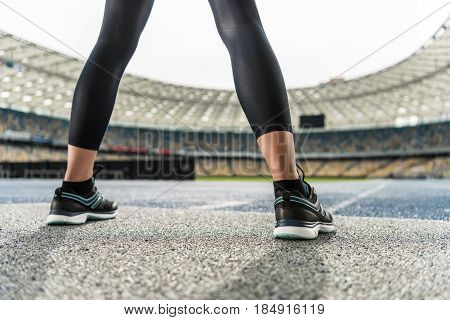 Close-up partial view of young sportswoman in sneakers standing on running track stadium