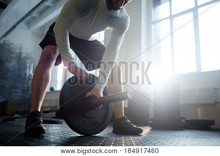 Low section portrait of strong muscular man putting heavy plates on barbell during workout in gym lit by sunlight