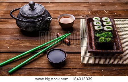 Photo of rolls, sticks, tea on wooden table
