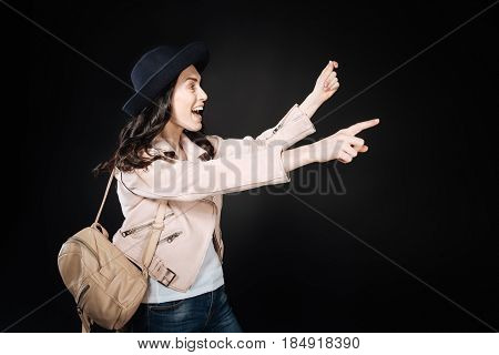 I found it. Happy brunette wearing stylish hat holding fictitious map in left hand while keeping backpack on the right shoulder