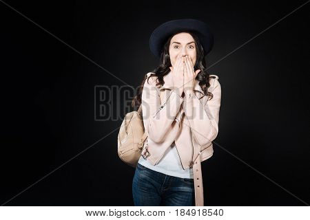 Dreams come true. Effective young woman covering her mouth looking at camera while standing over black background