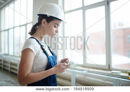 Side view portrait of young woman wearing uniform and hardhat working on construction site, watching video on digital tablet by window