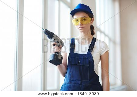 Portrait of young confident woman working with power drill installing windows on construction site