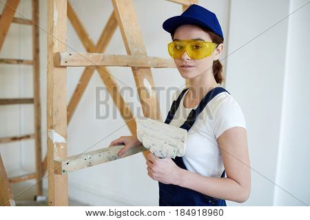 Portrait of smiling young woman doing plaster coating of walls,  looking at camera and smiling standing by wooden ladder  on construction site