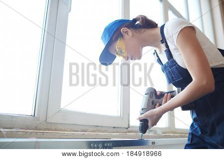 Side view portrait of young woman working with power drill, installing PVC windows