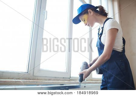 Side view portrait of young woman working with power drill, installing windowsills on construction site