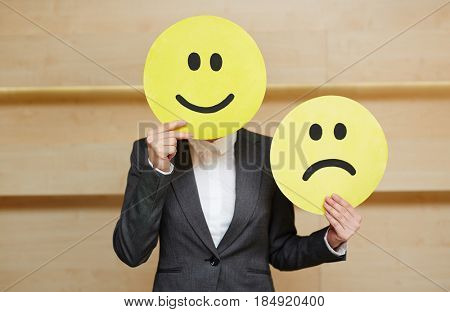 Unrecognizable businesswoman in formalwear covered her face with smiling mask while holding sad one in hand, waist-up portrait