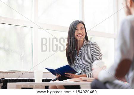 Pretty Asian manager looking at her male colleague with wide smile while having business meeting in office lobby with panoramic windows, portrait shot