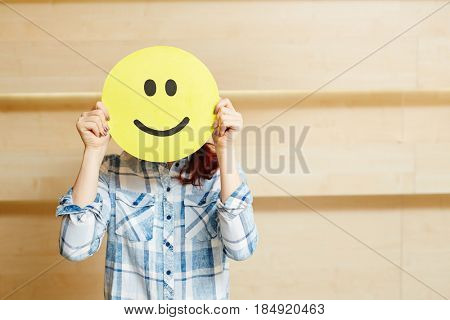 Unrecognizable young woman in checked shirt hiding her face under smiling mask while standing against wooden wall, waist-up portrait