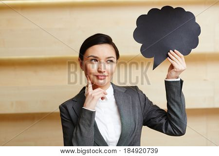 Waist-up portrait of pensive young entrepreneur looking away while holding speech bubble sign in hand