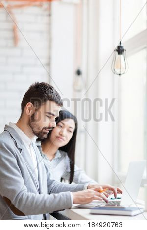Pretty Asian businesswoman and her handsome bearded colleague brainstorming on joint project while sitting in cozy coffeehouse, waist-up portrait