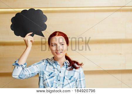 Pretty red-haired woman in checked shirt looking away with toothy smile while holding speech bubble sign in hand, waist-up portrait