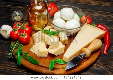 traditional italian products parmesan or parmigiano and mozarella on cutting board isolated on white. clipping path embeeded