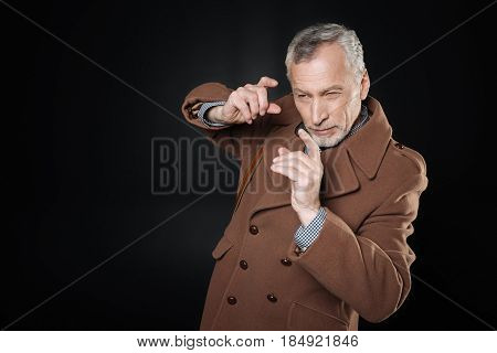 I am photographer. Attentive gray-haired man looking narrowly through hands wrinkling forehead while standing in semi position