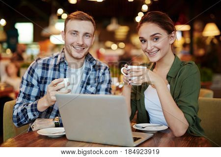 Two young friends posing for photography with toothy smiles while hanging out in small cozy coffeehouse, waist-up portrait