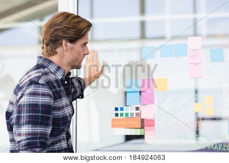 Businessman looking at plan on glass wall in office