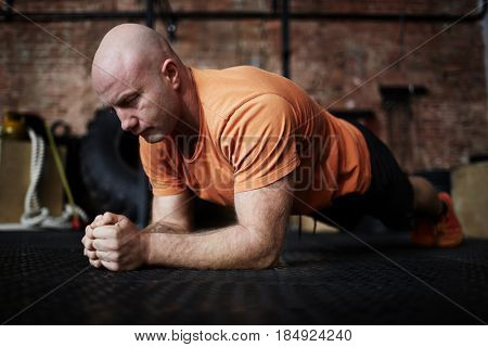 Bald middle-aged bodybuilder standing in plank during intensive workout in modern gym, full-length portrait